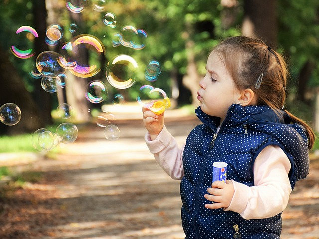 Young girl blowing bubbles outside.