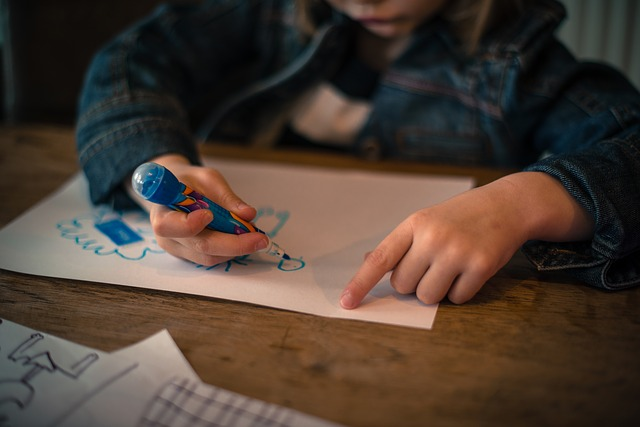 Child drawing on a piece of paper with a marker at a desk.